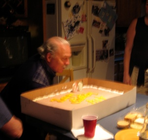 A blurry photo of my dad blowing out his candles.